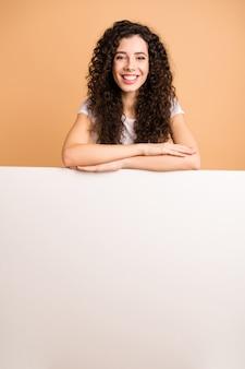 空の割引バナーに手を寄りかかっている素晴らしい女性の写真白いプラカードオファーバイヤー安い広告着用白いカジュアルな服分離ベージュパステルカラーの背景