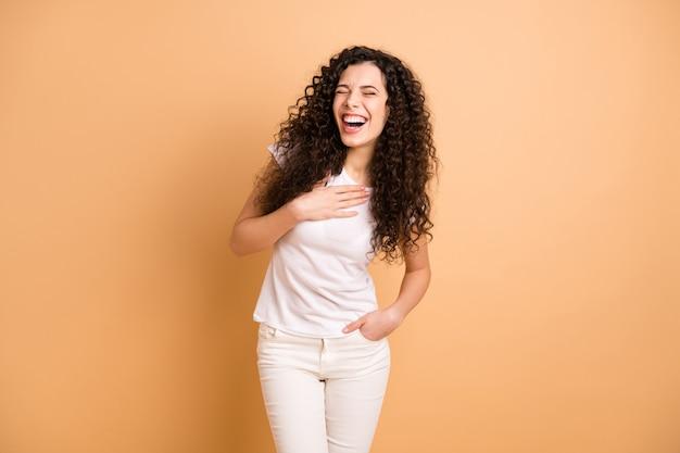 Фотография удивительной женщины, слушающей отличную юмористическую историю, держась за руку на груди, громко смеясь, носить белую повседневную одежду, изолированную бежевым пастельным цветом фона