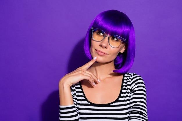 驚くべき女性タッチあご指の写真空のスペースを見て明るいかつらストライププルオーバー孤立した紫色の背景を着用してください