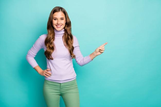 Фотография удивительной симпатичной дамы указывает пальцем на пустое место, советуя распродажу новинки, низкие цены, носить фиолетовый сиреневый пуловер зеленые брюки, изолированные пастельно-бирюзового цвета