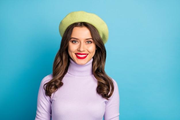 素晴らしい旅行者の女の子の女性の歯を見せる笑顔のスタイリッシュな外観の写真は、モダンな緑色のベレー帽の帽子紫のタートルネックのジャンパー分離された明るい青色の壁を着用します