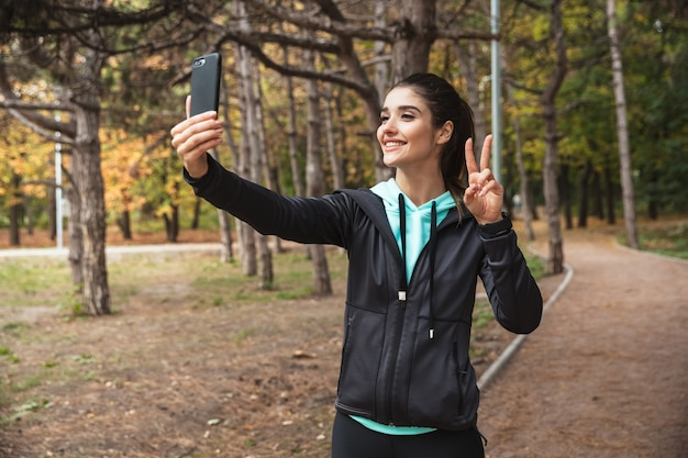 携帯電話を使用して公園の屋外で驚くべき若いかなりフィットネスの女性の写真は、平和のジェスチャーで自分撮りを取ります。