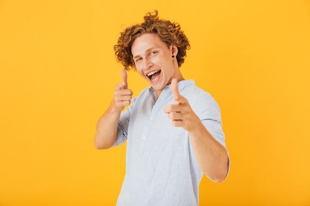 黄色の背景の上に分離された、笑顔であなたに指を指している面白いハンサムな男の写真