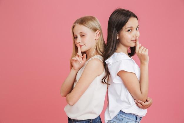 입술에 검지 손가락을 들고 분홍색 배경 위에 절연, 침묵 또는 비밀을 유지하도록 요구하는 캐주얼 의류를 입고 8-10 세의 재미있는 어린 소녀의 사진