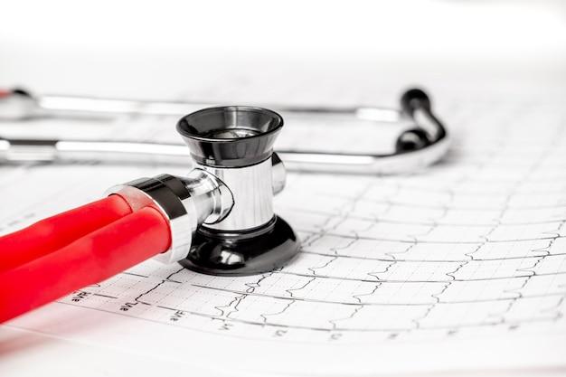 Фотография электрокардиограммы экг или распечатка экг со стетоскопом. концепция медицинского здоровья. аускультация, прослушивание пульса сердца с помощью стетоскопа