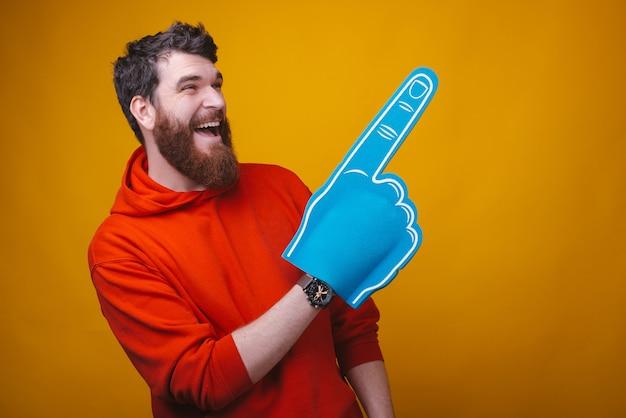 Фотография возбужденного бородатого мужчины носит голубую перчатку вентилятора пены, заставляющую вас качать это жест.