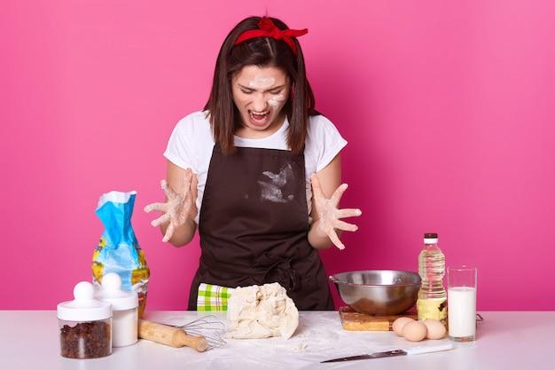 カジュアルなtシャツと小麦粉で汚れた茶色のエプロンに身を包んだ、混練生地にうんざりして疲れている怒っているブルネットのパン屋の写真。女性は何かを叫びながら指を広げます。食品のコンセプト。