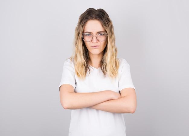 화가 심술 젊은 백인 여성의 사진은 부담없이 엄격하고 회의적인 표정으로 접힌 팔을 유지하는 옷을 입고