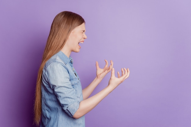 화난 미친 여자가 비명을 지르는 사진은 보라색 배경에 짜증스러운 분위기를 자아낸다