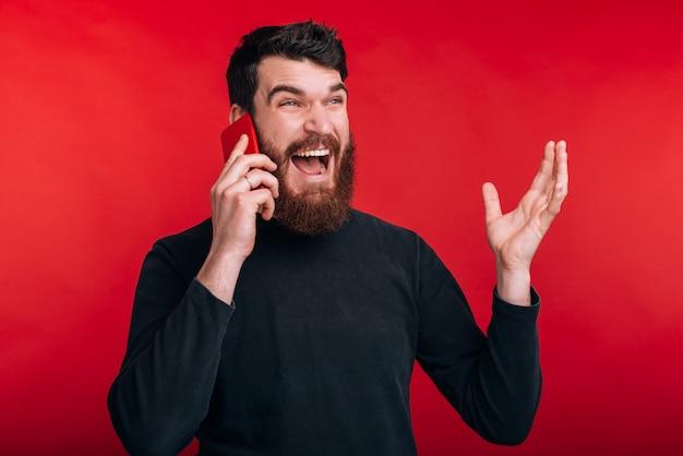 Фото злой человек кричать и говорить на смартфоне, стоя над красным пространством