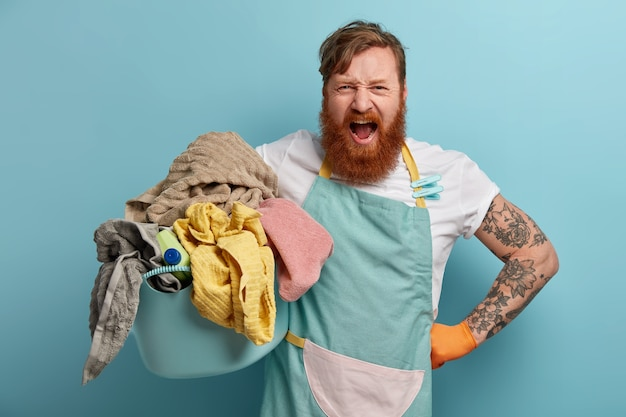 집안일로 바쁜 성가신 수염 난 남자의 사진, 세탁물과 세제로 가득 찬 바구니를 들고, 앞치마를 입고, 큰 소리로 외치고, 파란색 벽에 고립 된 귀찮은 느낌, 세탁에 지쳤습니다.