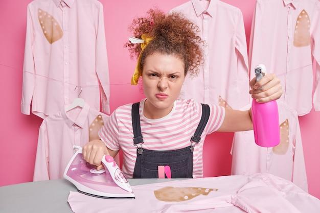 Фотография раздраженной европейской женщины с кудрявыми волосами и ухмылкой на лице выглядит несчастной, держит бутылку с распылителем, делает домашнюю работу, гладит одежду, одетая небрежно. концепция домашних обязанностей