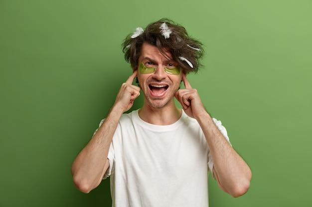 イライラした男の写真は、耳と叫び声を差し込んで、沈黙を要求し、大きな音のために目が覚め、白いカジュアルなtシャツを着て、目の下に保湿パッチを着て、朝の気分が悪く、緑の壁に隔離されています