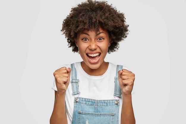 イライラした憤慨した黒人の若い女性の写真は怒りで拳を食いしばり、アフロの髪型をしています