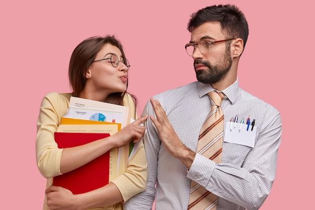 그녀를 막으려는 잘 생긴 남자에게 키스하고 싶어하는 매력적인 돌보는 여성의 사진, 거절 제스처