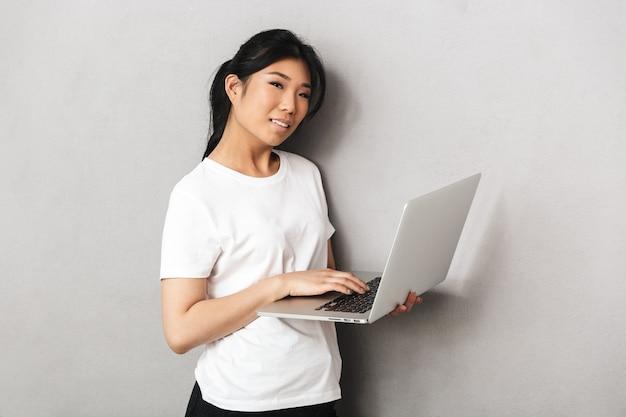 Фотография азиатской красивой молодой женщины позирует изолированной над серой стеной с помощью портативного компьютера.
