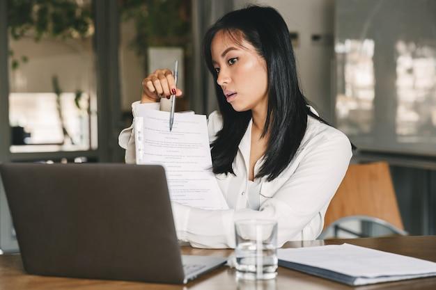 화상 통화 또는 온라인 회의 중에 사무실 의류를 들고 노트북 화면에 종이 문서를 보여주는 아시아 비즈니스 여성 20 대의 사진