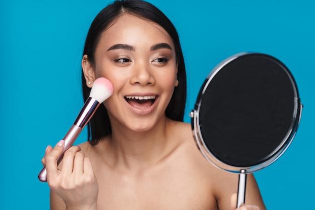 Фотография азиатской счастливой позитивной молодой женщины, позирующей изолированной на синей стене, наносит румянец с щеткой, держащей зеркало.