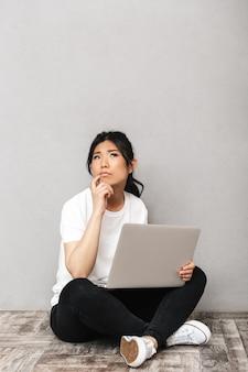 ラップトップコンピューターを使用して灰色の壁に隔離されたポーズをとってアジアの思考の美しい若い女性の写真。