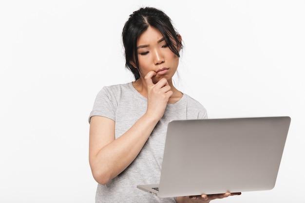 ラップトップコンピューターを使用して白い壁に隔離されたポーズをとってアジアの思考の美しい若い女性の写真。