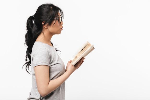 本を読んで保持している白い壁の上に孤立してポーズをとってアジアの思慮深い美しい若い女性の写真。