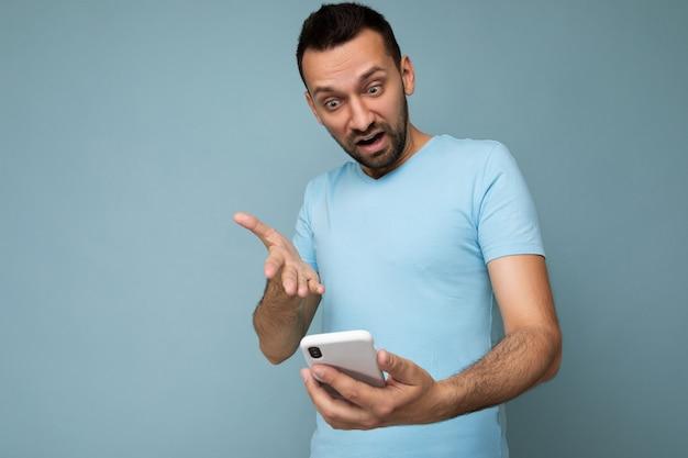 孤立した毎日の青いtシャツを身に着けているひげを持つ不満のハンサムな若い男を尋ねる写真
