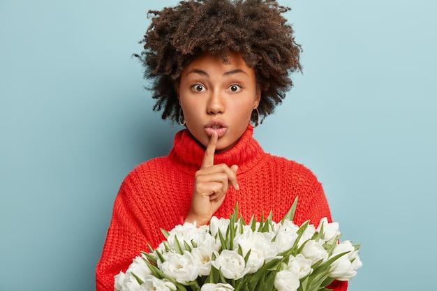 驚いた美しい女性の写真は、沈黙のジェスチャーをし、唇の上に前指を保ち、ニットの赤いジャンパーを着て、青い壁に隔離された白い春の花を持っています。ハッシュ記号。秘密を言わないで
