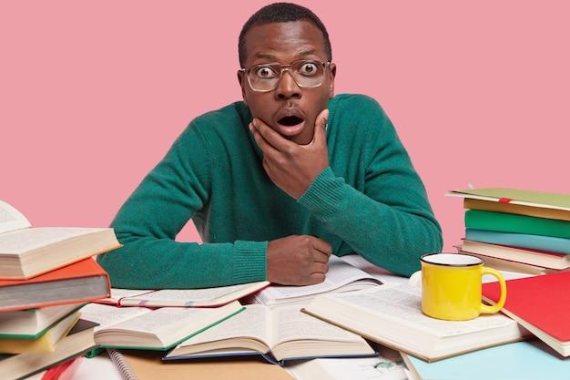 驚いた黒人の若い男の写真は、あごを持って、信じられないほど見つめ、テーブルの周りにたくさんの本を開いています