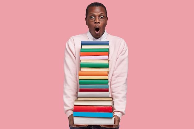 흰색 캐주얼 점퍼에 놀란 흑인 젊은 남자의 사진은 책 더미를 운반하고, 둥근 안경을 착용하고, 분홍색 벽에 서 있습니다.