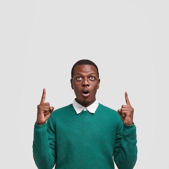 Фотография удивленного темнокожего молодого человека показывает указательными пальцами к потолку, удивленно открывает рот.