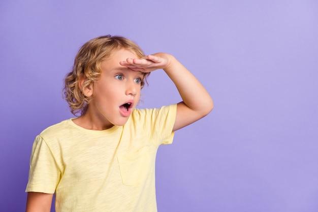 Фотография изумленного мальчика с взглядом copyspace положила руку на лицо глаз, изолированное на фиолетовом фоне