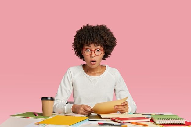 Фотография удивленной смуглой молодой женщины затаив дыхание, читает неожиданную информацию в бумажных документах.