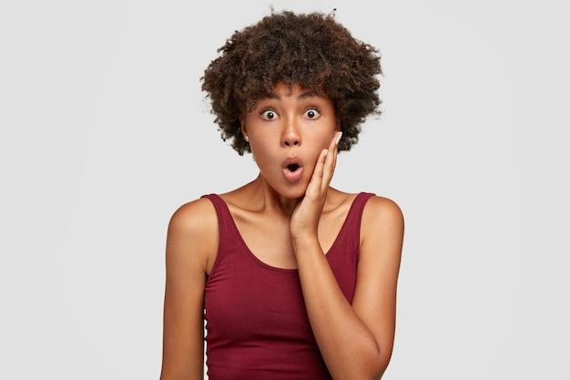Фотография изумленной этнической женщины с вытаращенными глазами, держит рот открытым, видит что-то невероятное