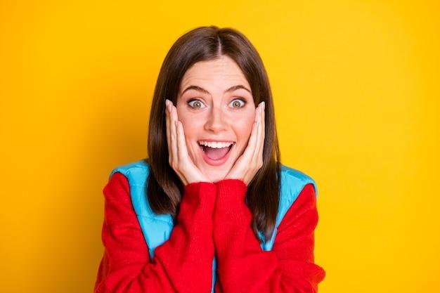 驚いた女の子の流行に敏感なタッチの手の顔の写真は、明るい輝きの色の背景の上に分離された素晴らしい季節の掘り出し物の赤いセーターを着ています