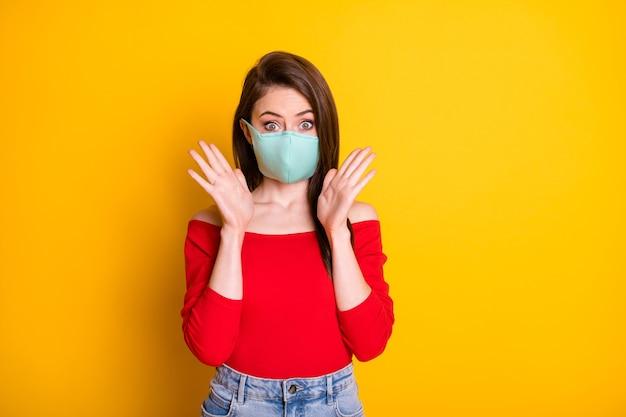医療マスクで驚いた女の子の写真は信じられないほどのcovidスプレッドストップ情報を印象づけました明るい輝きの色の背景の上に分離された赤いトップデニムジーンズを着用してください