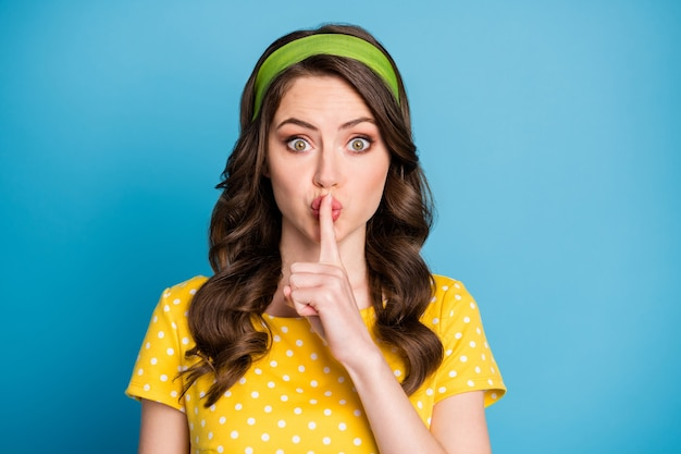 Фотография изумленной девушки положила указательный палец на рот, не рассказывая секретную концепцию, изолированную на синем фоне
