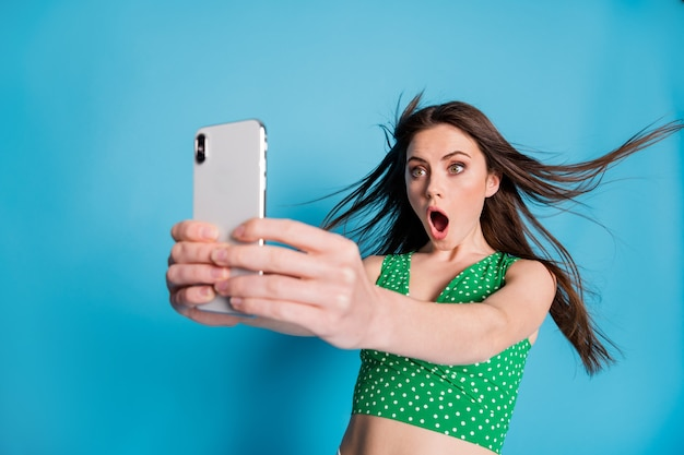 놀란 소녀가 스마트폰을 사용하는 사진은 빠른 속도의 5g 인터넷 연결에 깊은 인상을 받았으며 파란색 배경에 격리된 멋진 옷을 입었습니다.