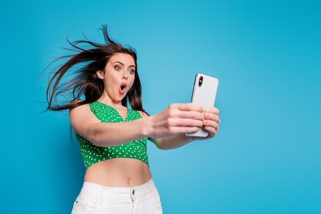 놀란 소녀가 스마트폰을 사용하는 사진은 빠른 속도의 무선 연결에 깊은 인상을 받았습니다. 파란 배경 위에 격리된 흰색 바지 바지를 입습니다.