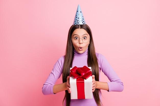 Фотография изумленной девушки-малышки в подарочной коробке в фиолетовой кепке на день рождения, изолированной на пастельном цветном фоне