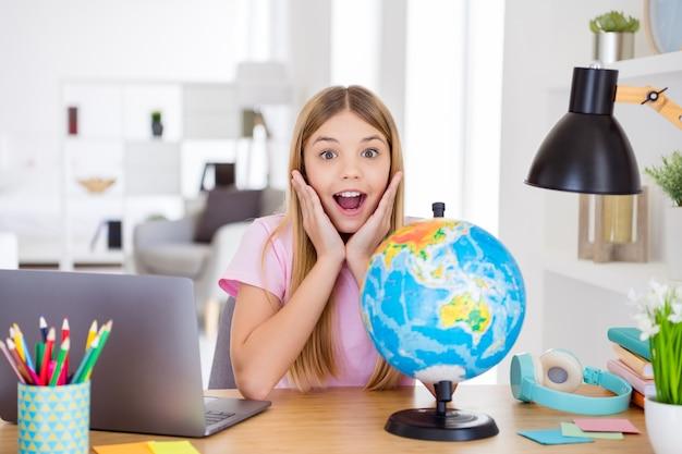 驚いた子供の女の子の研究地理リモート感動した新しい大陸の情報悲鳴を上げるタッチ手顔面騎乗快適なテーブルデスクの家の屋内