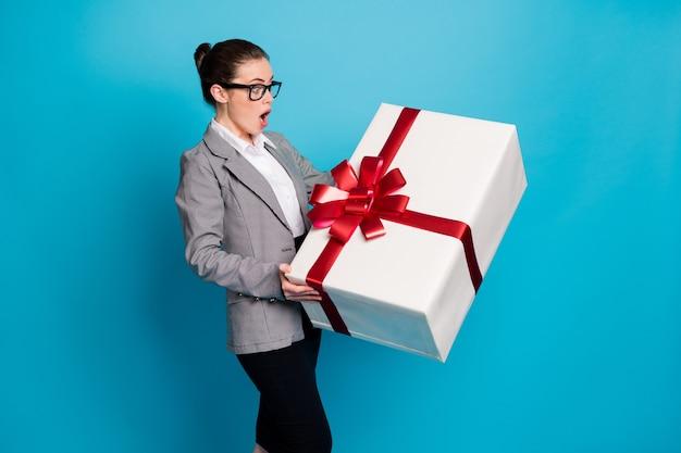 Фотография изумленной девушки-менеджера-босса получает огромный подарок в серых пиджаках, юбке, изолированном синем цветном фоне