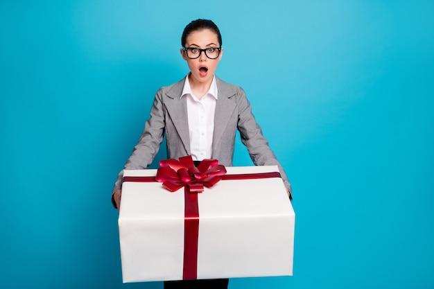 Фотография изумленной представительной девушки держит огромную подарочную коробку в сером пиджаке, изолированном синем цветном фоне