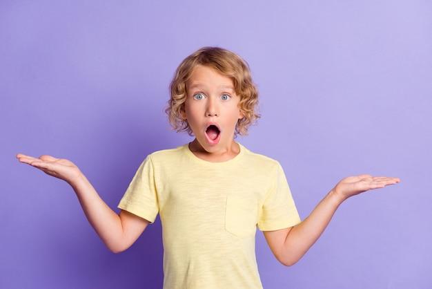 Фотография удивленного маленького мальчика, взявшегося за руки, носит одежду в повседневном стиле, изолированную на фиолетовом цветном фоне