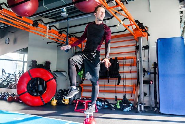 Фотография спортсмена держит равновесие стоя, поставив одну ногу на гирю
