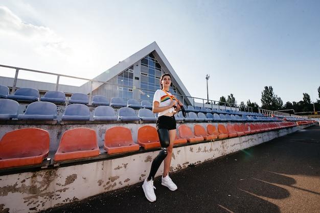 Фотография спортивной девушки-инвалида с бионической ногой в спортивной одежде, стоящей и улыбающейся на улице над бетонной стеной
