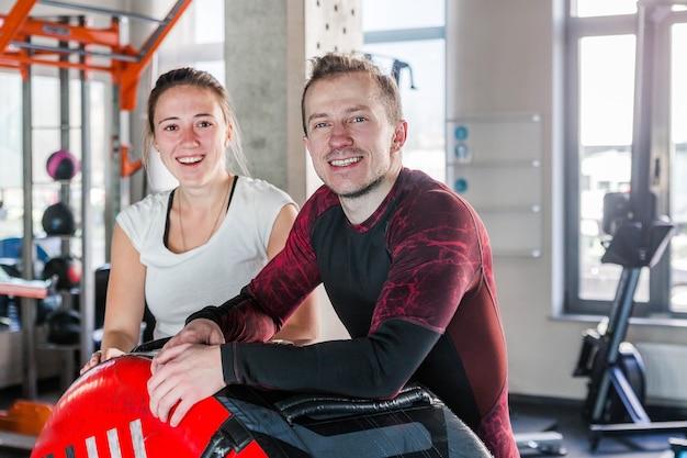 Фотография спортивного мужчины и женщины в тренажерном зале, улыбаясь и глядя в камеру. горизонтальное фото