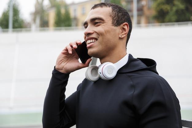 雨の後にスタジアムで運動しながら携帯電話を話しているトラックスーツの運動笑顔のスポーツマンの写真