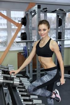 체육관에서 아령으로 운동을 하는 운동 어린 소녀의 사진