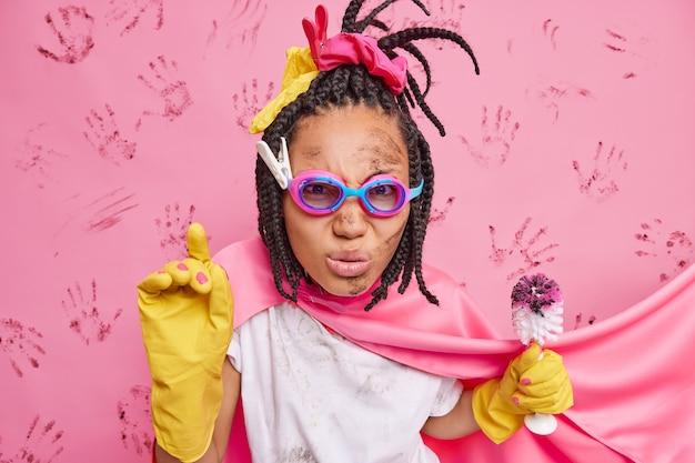 세심한 진지한 주부의 사진은 고글 슈퍼 히어로 망토를 착용하고 고무 장갑은 분홍색 벽 위에 격리 된 가사 업무로 바쁜 화장실 청소를위한 브러시를 보유하고 있습니다.
