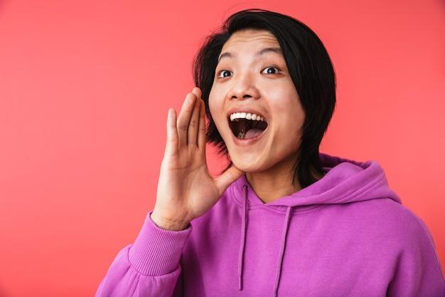Фотография привлекательного азиатского парня в толстовке, радующегося, кричащего или называющего кого-то изолированного над красной стеной